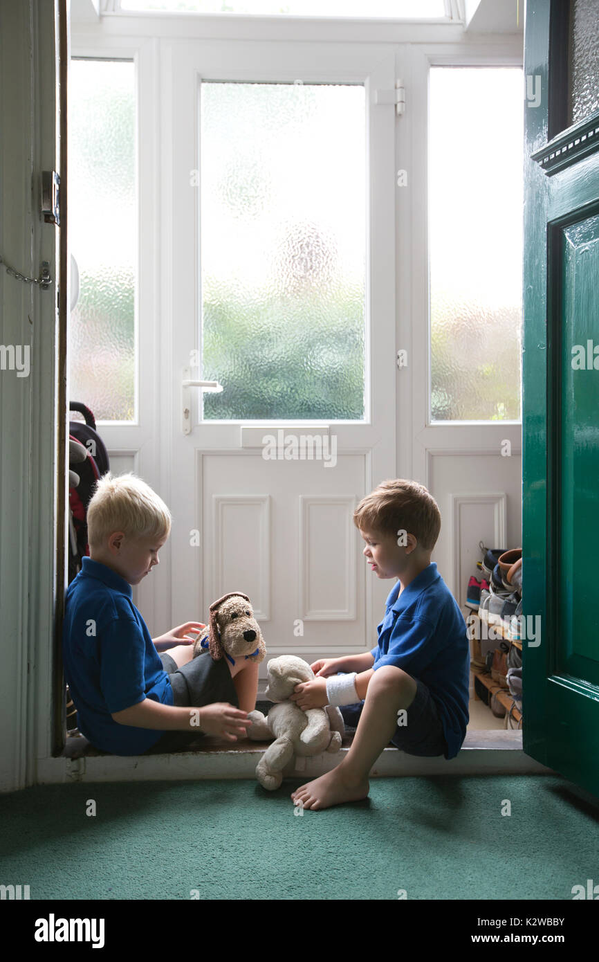 3 year old and 6 year old boys sitting in a residential doorway dressed in uniform ready to go back to school, London, England, UK - Stock Image