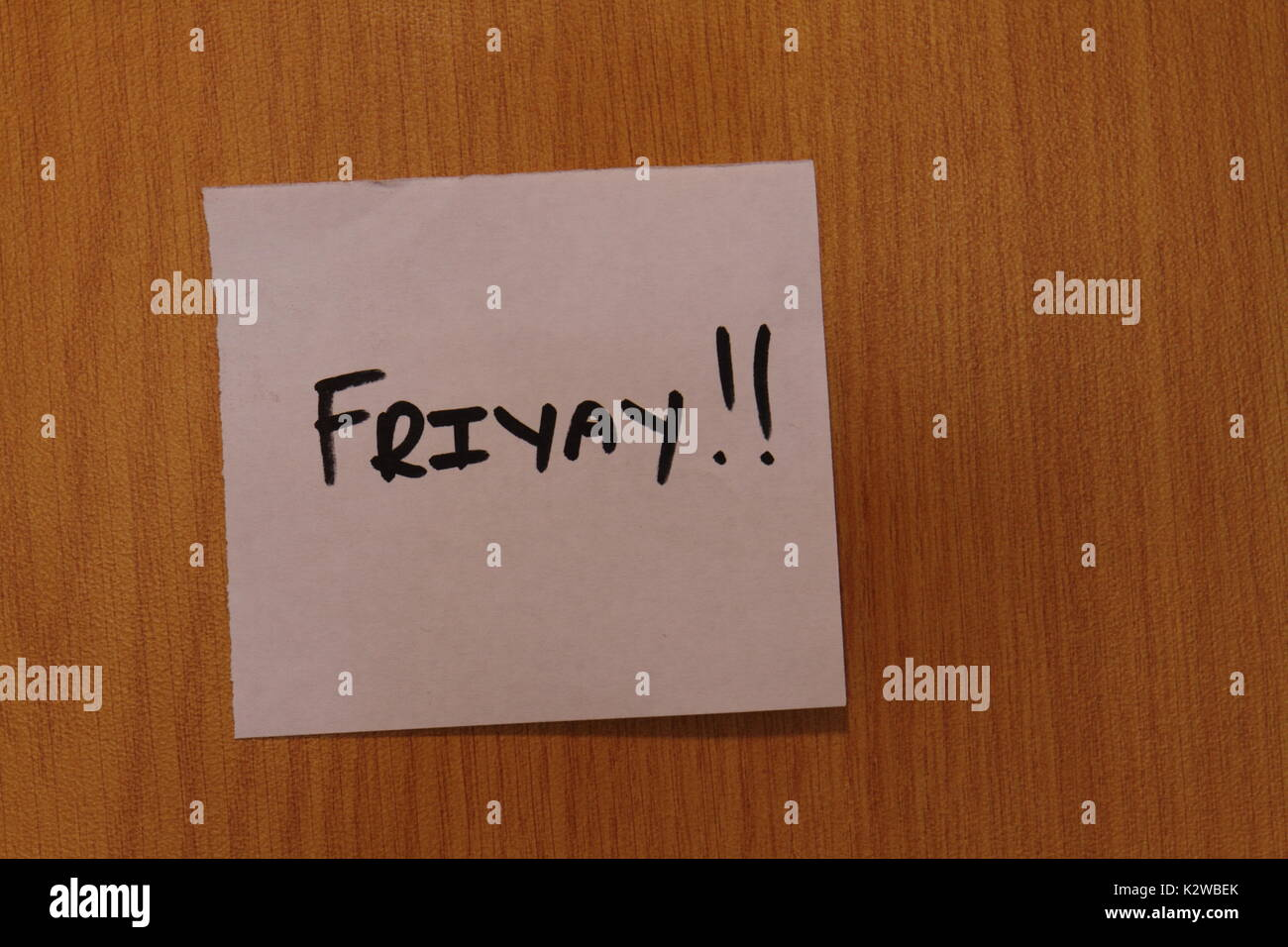 The term Friyay displayed on a hand written note stuck to a wooden notice board in landscape format with a clear background and copy space - Stock Image