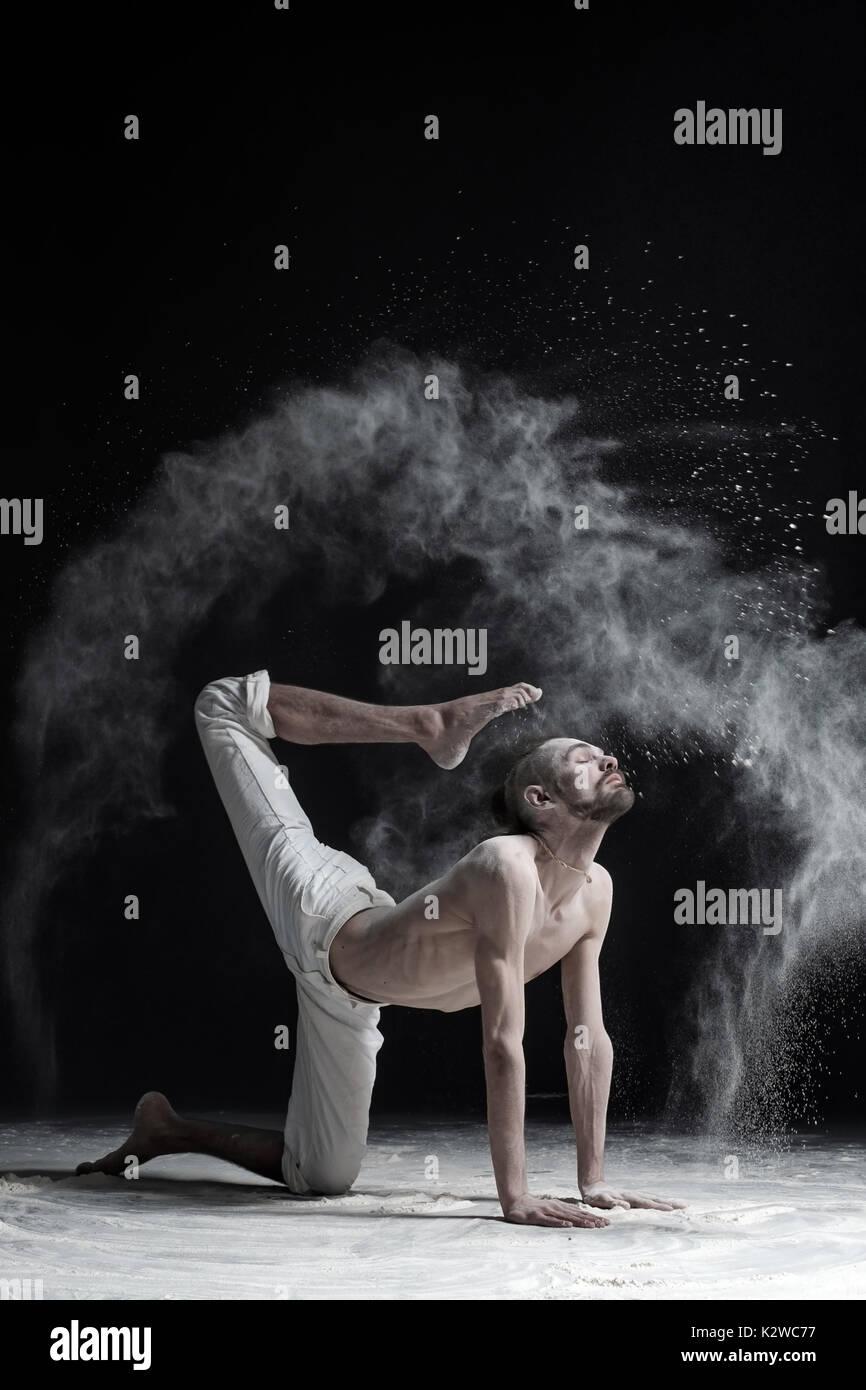 A yoga teacher sits in a sukhasana on a black background. - Stock Image