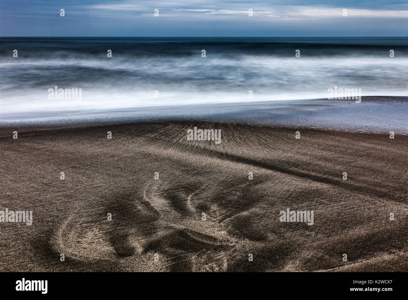 primordial footprint on the sand in front of the sea - Stock Image