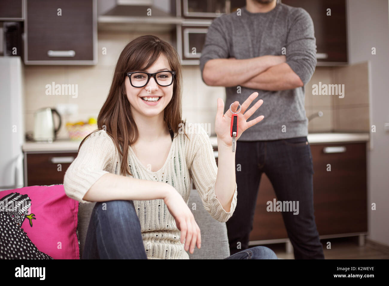 Cheerful smiling woman with car keys and a distrustful man standing behind her with crossed hands - Stock Image
