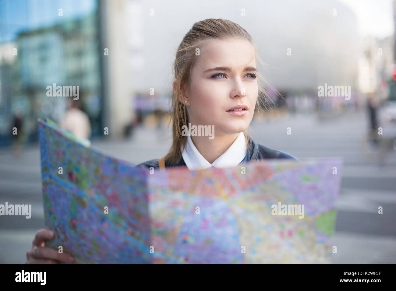 Woman with city map lost in big city - Stock Image