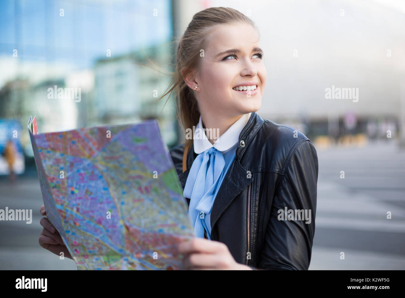 Smiling woman with city map in city - Stock Image