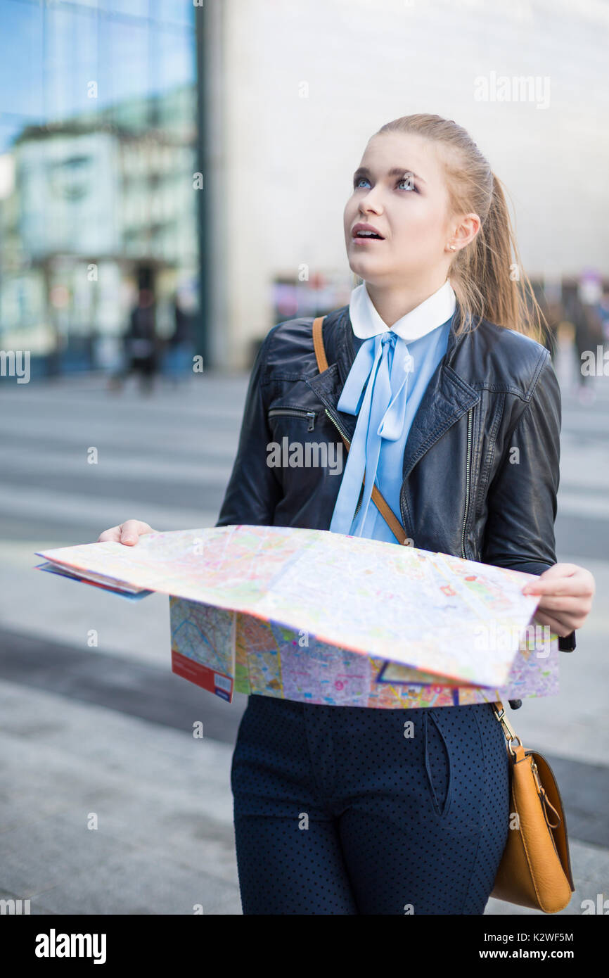 Confused woman with map in city - Stock Image