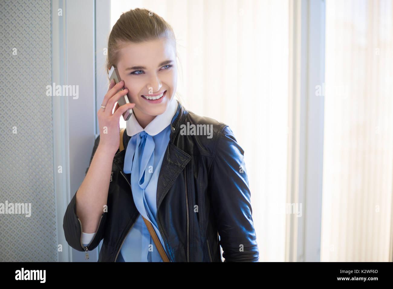 Smiling woman having nice phone conversation - Stock Image
