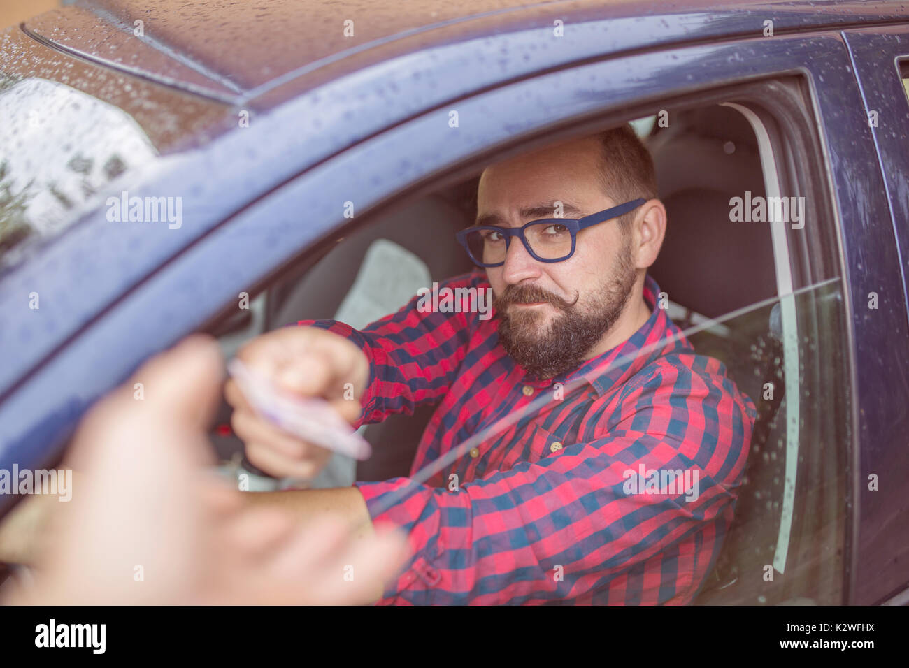 Man sitting in car and giving his driving licence through the window - Stock Image