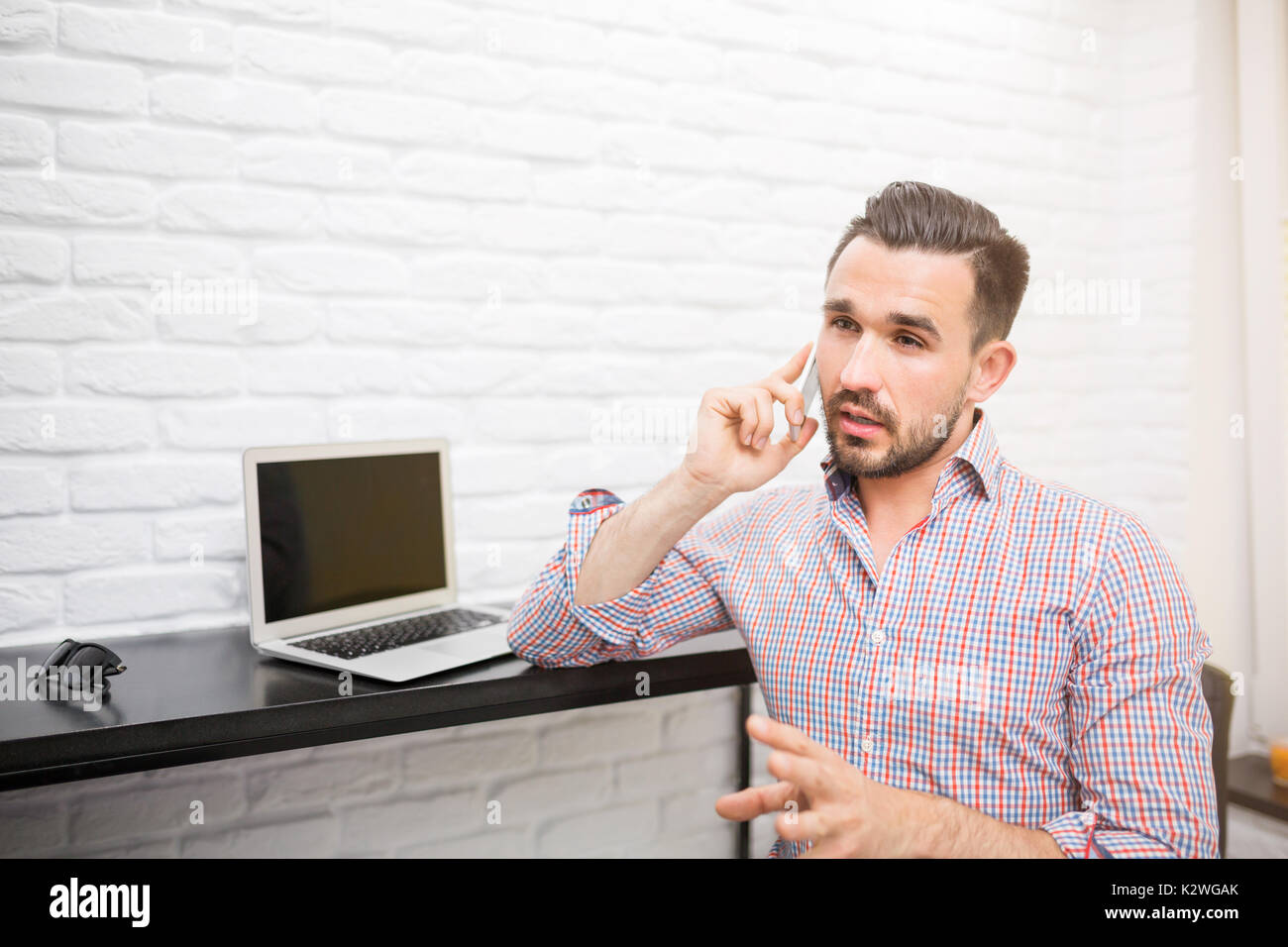 Young man carrying out negotiations by the phone in his home office. - Stock Image