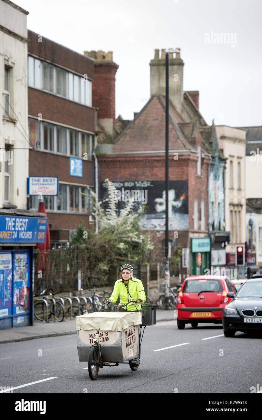 Bread delivery cyclist in Stokes Croft, Bristol UK - Stock Image