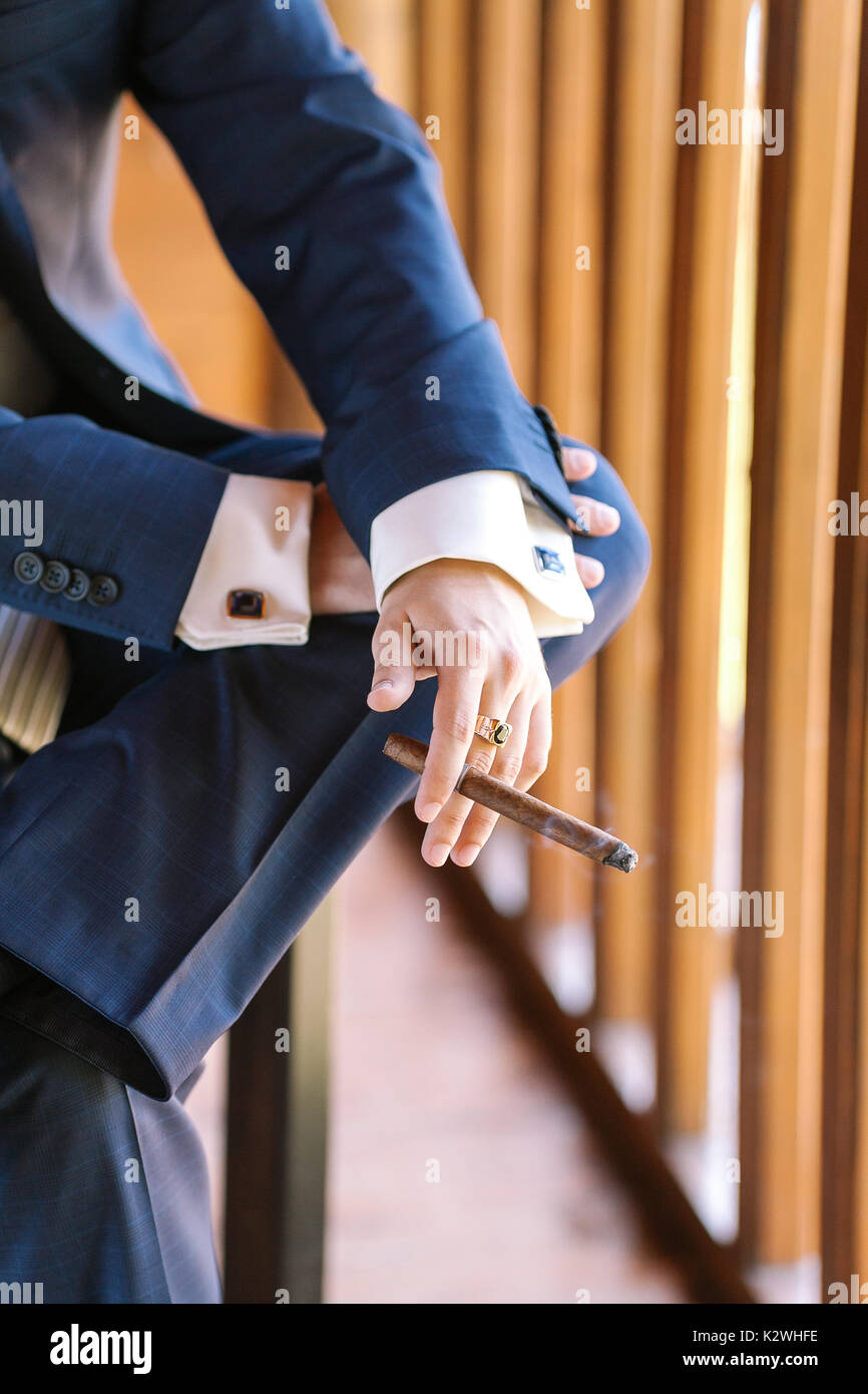 virility, solvency, business concept. close up of arms of young wealthy man wearing blue tweed suit with wondreful cufflinks, crossing his legs and smoking cigar - Stock Image