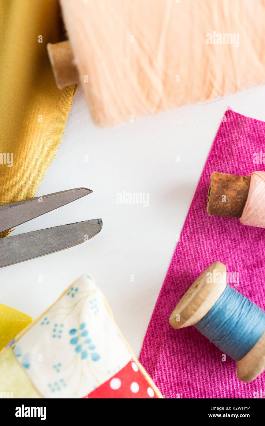 sewing, patchwork, tailoring and fashion concept - closeup tools on white work desk in studio, scissors, spools of blue and pink threads, pincushion, pieces of colored patchwork fabric, vertical. Stock Photo