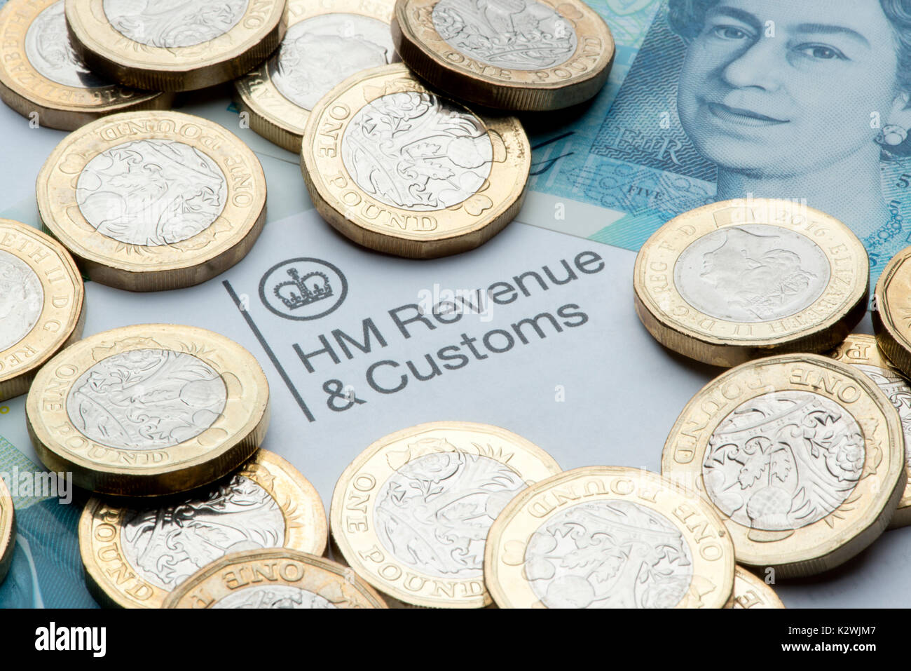 An HM Revenues & Customs letterhead surrounded by new £1 coins and a £5 note. - Stock Image