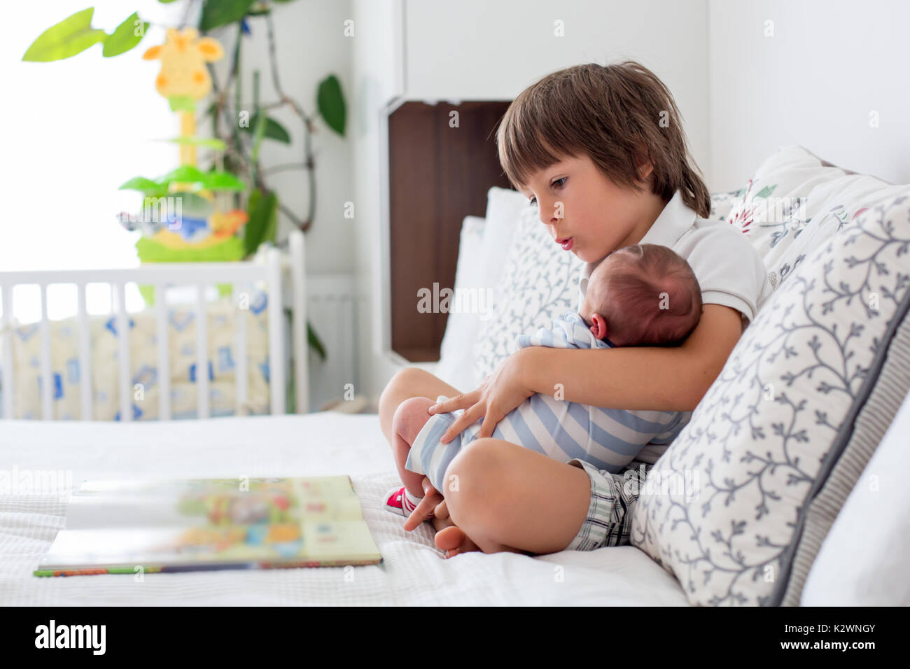 Sweet preschool boy, reading a book to his newborn brother, sitting on the bed in bedroom, childhood concept Stock Photo