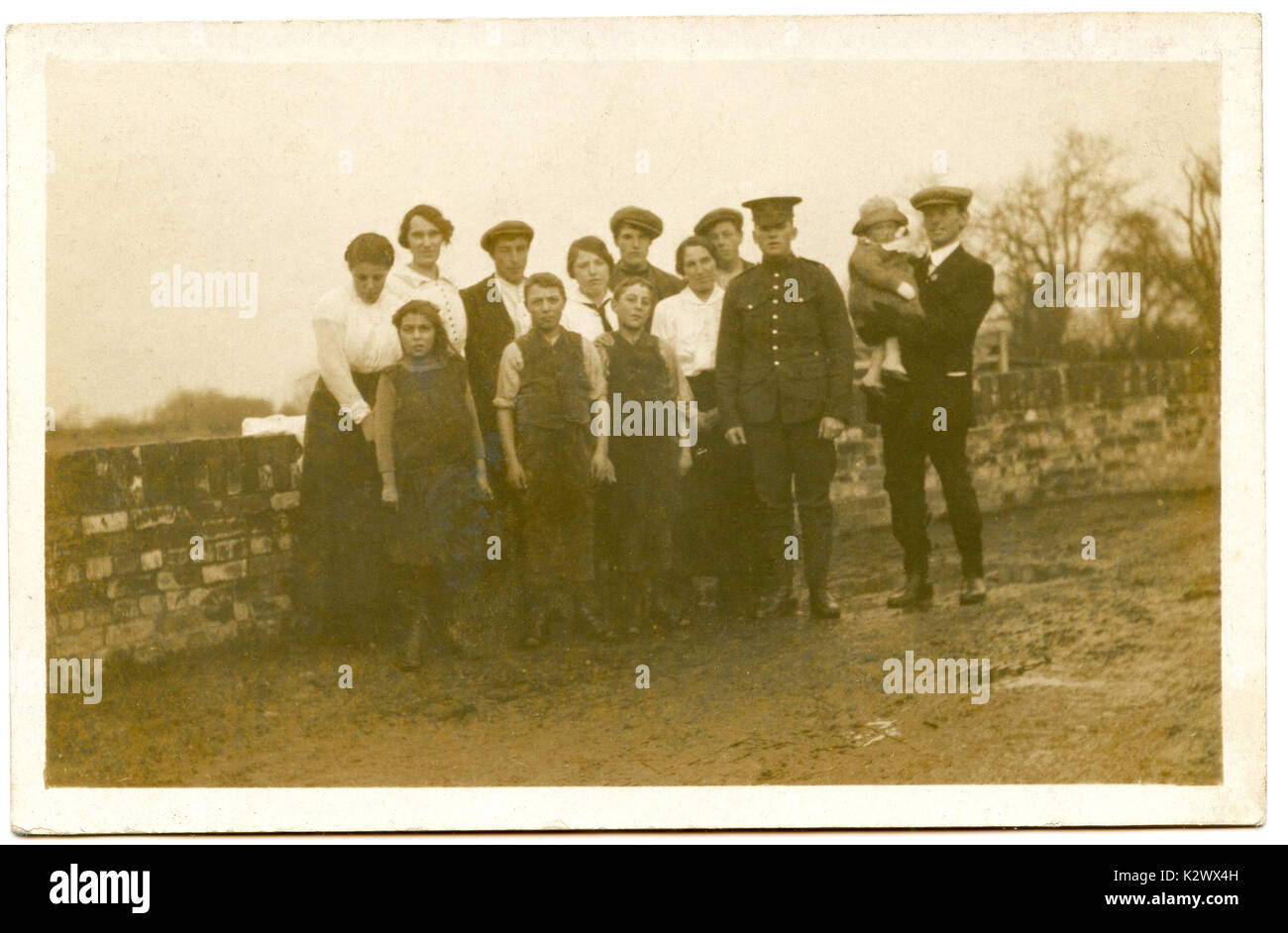 @ 1915, historical photo postcard from Britain, showing a young male soldier in uniform proudly posing with his extended family before heaiding off to fight in WW1. - Stock Image