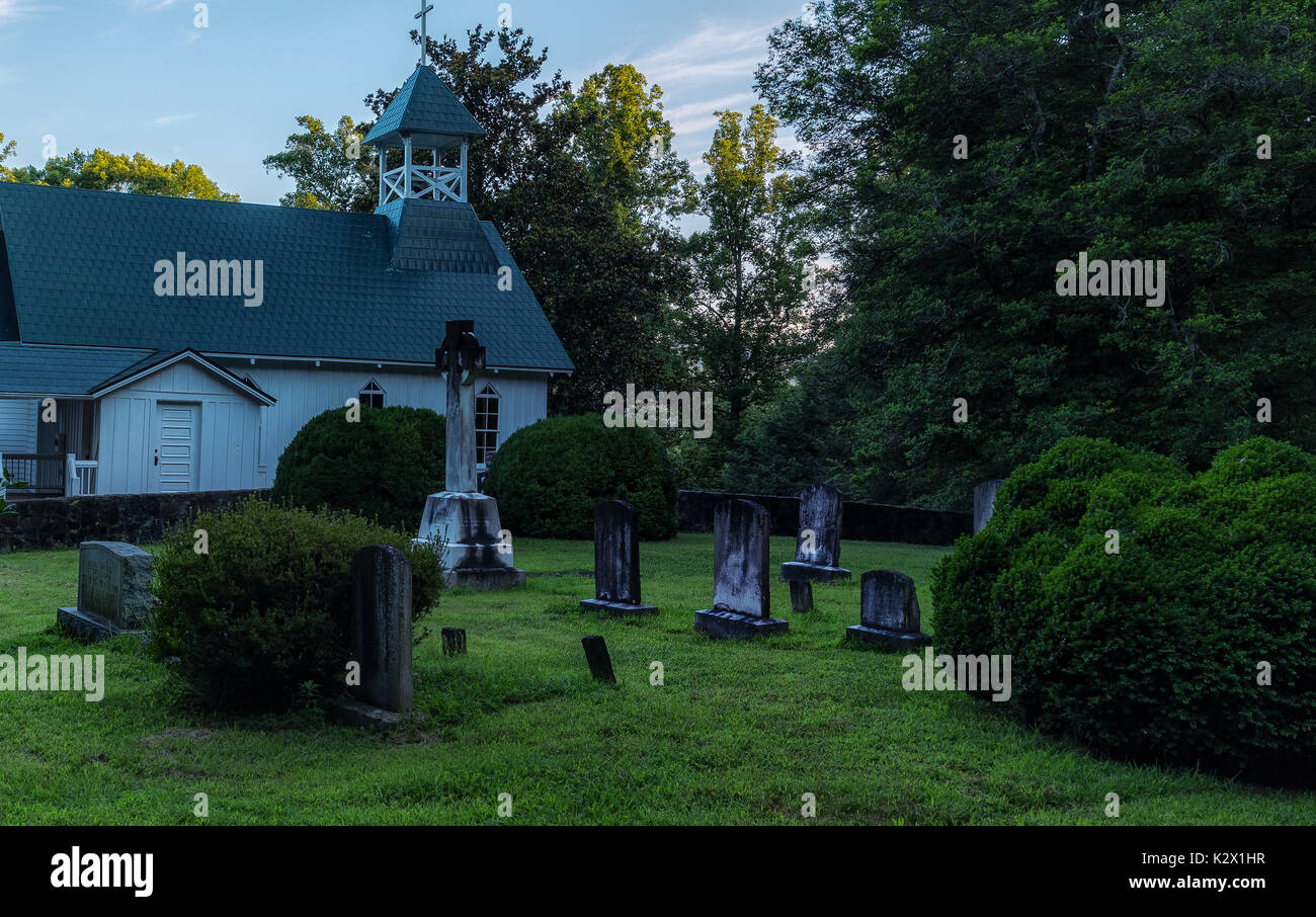 Old Church Graveyard NC Chapel Of Rest - National Registry Historical Locations. Graveyard at dusk with old worn graves and church steeple in back. - Stock Image