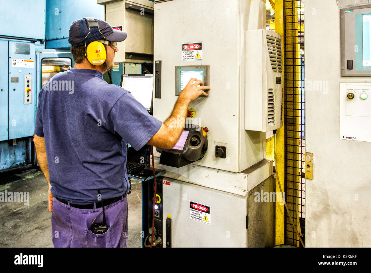 Bluecollar worker operating an equipment. Guaramirim, Santa Catarina, Brazil. Stock Photo