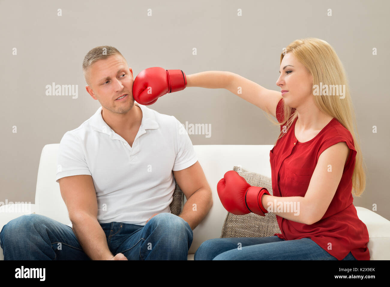 Portrait Of Young Couple Sitting On Sofa Fighting With Boxing Gloves - Stock Image