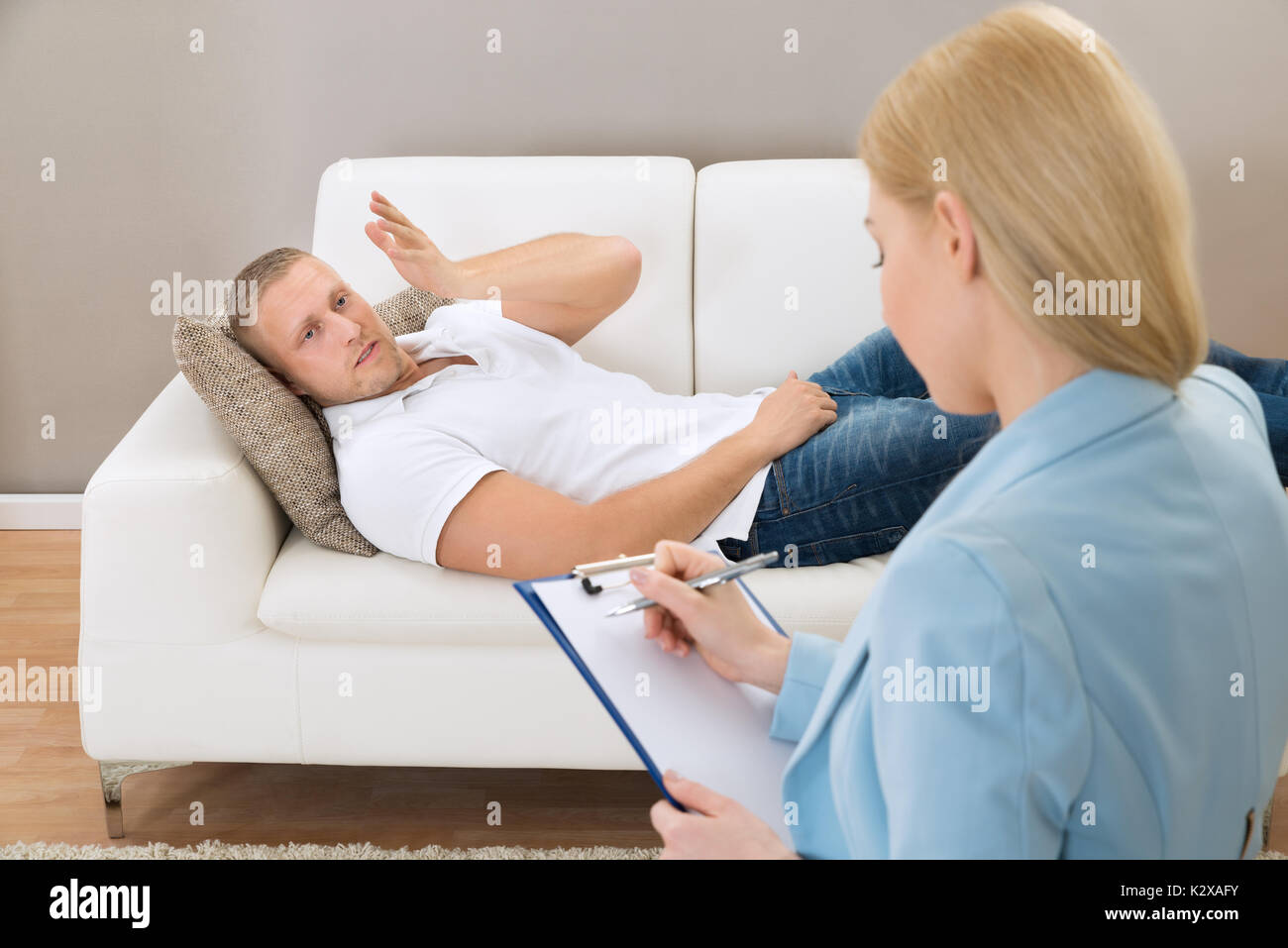 Female Psychologist Making Notes During Psychological Therapy Session - Stock Image