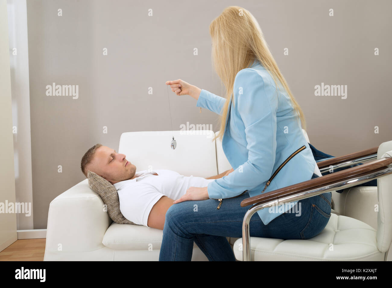 Female Psychiatrist Hypnotizing Patient Lying On Couch - Stock Image