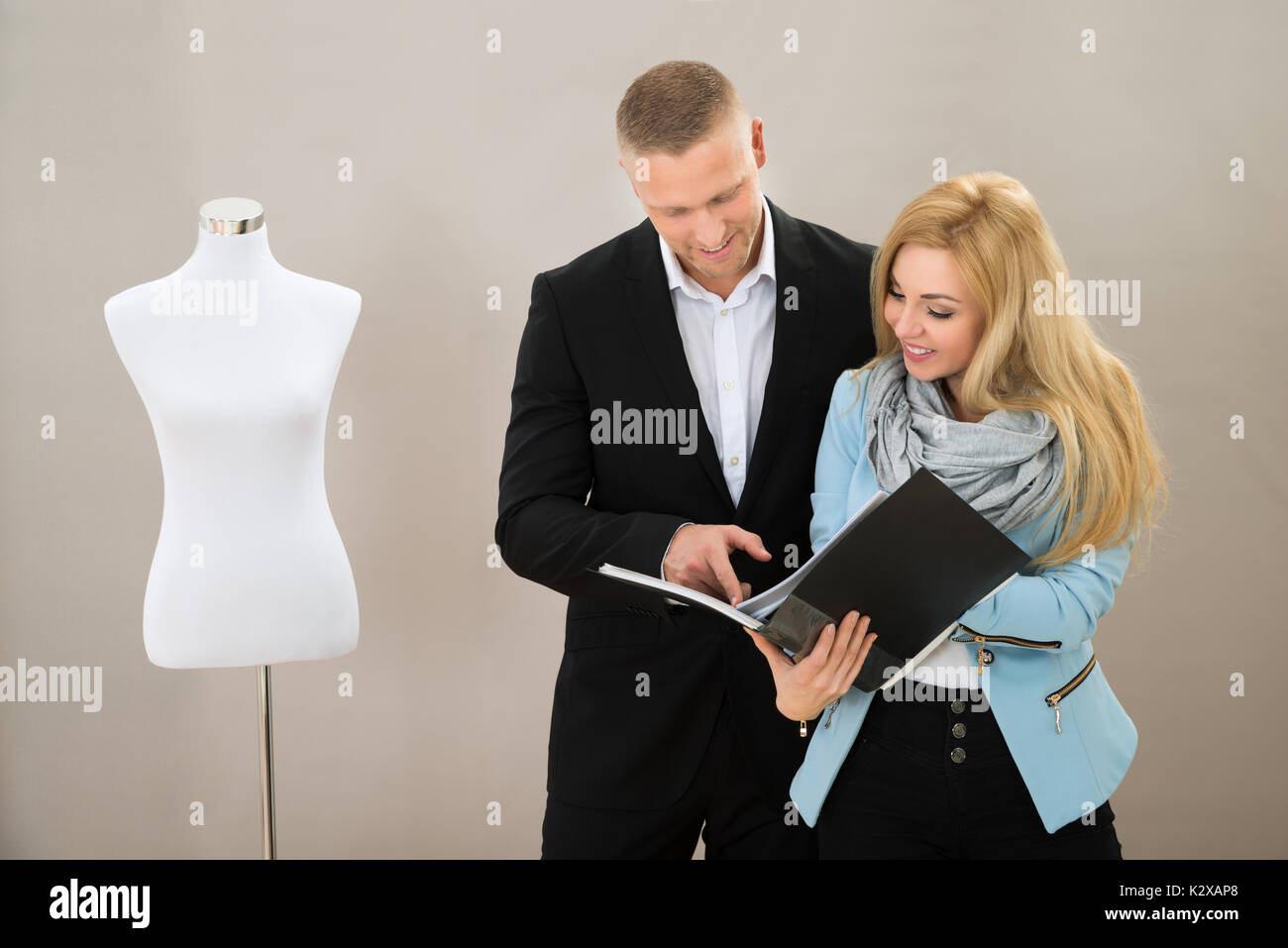 Young Female Tailor With Male Client Looking At Catalogue In