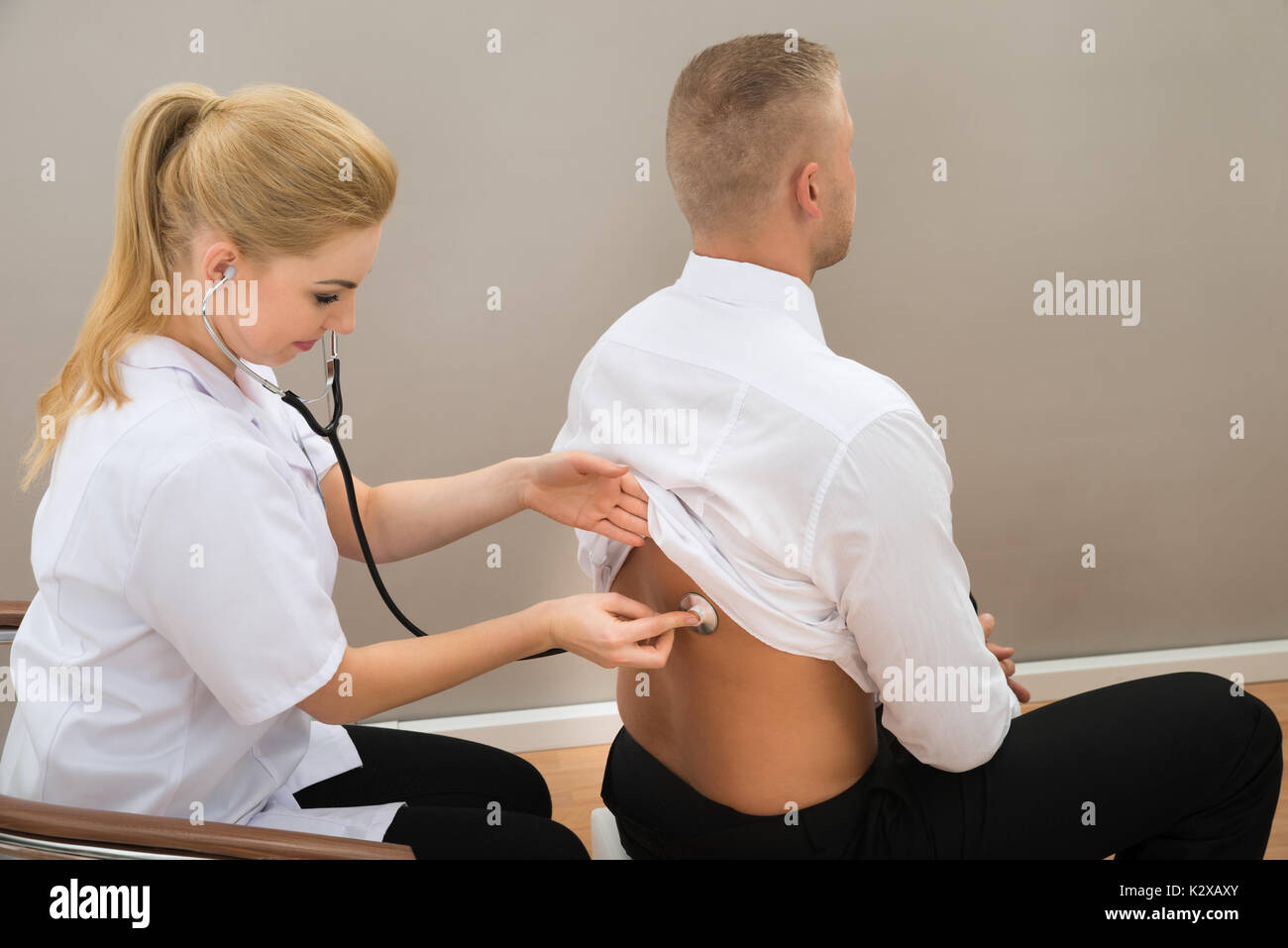 Female Doctor Examine Patient's Back With Stethoscope - Stock Image