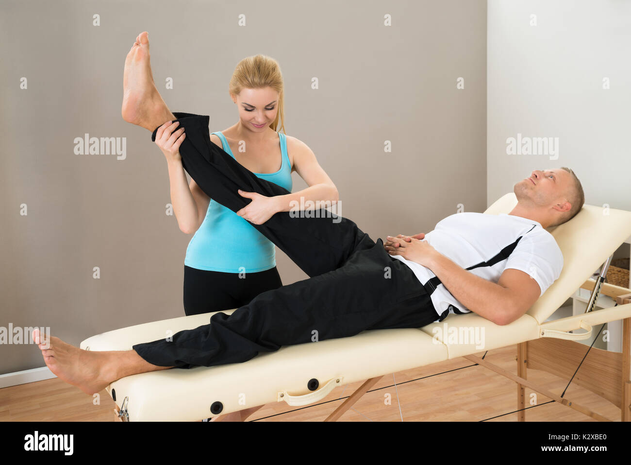 Young Female Instructor Helping Man For Doing Exercising - Stock Image