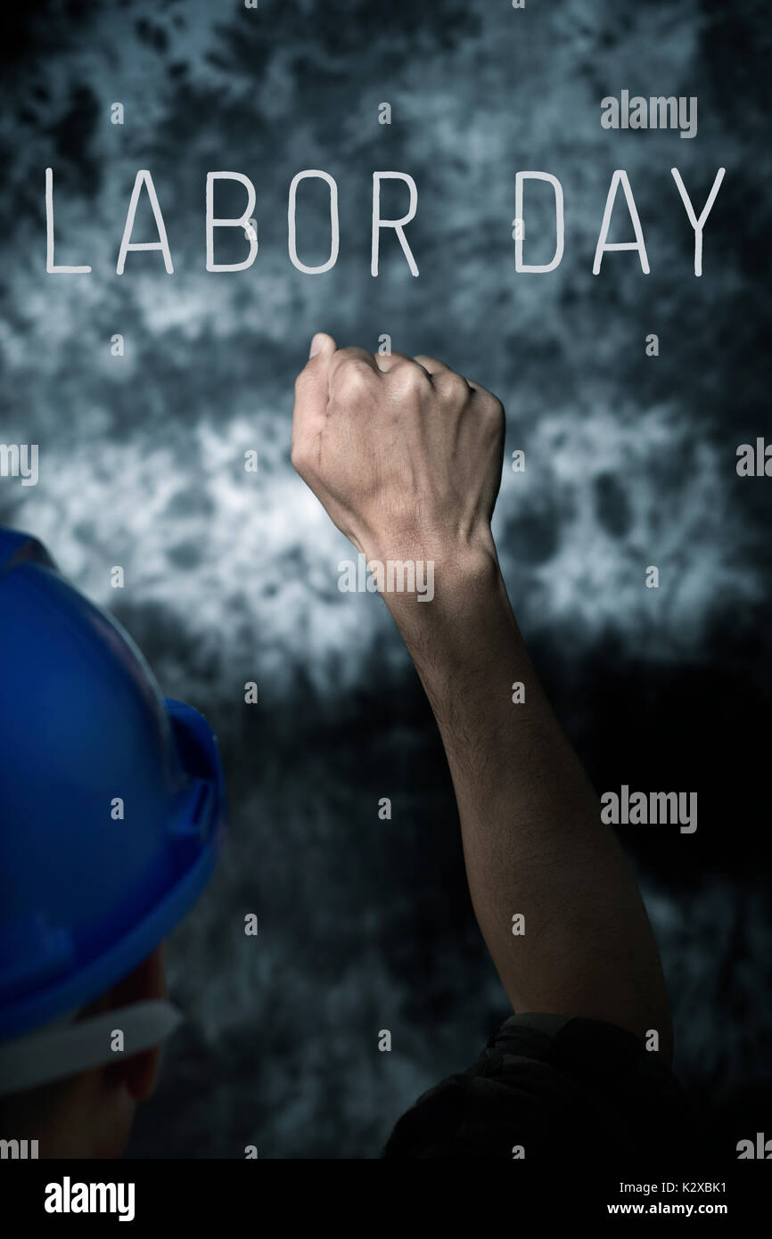 closeup of a young caucasian man seen from behind wearing a blue hard hat and with his fist raised to the air, against a gradient gray background and  - Stock Image