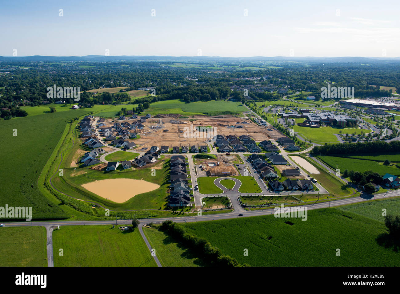 URBAN SPRAWL AERIAL VIEW OF HOUSING DEVELEPMENT UNDER CONSTRUCTION NEXT TO AGRICULTURAL FIELDS, LITITZ PA - Stock Image