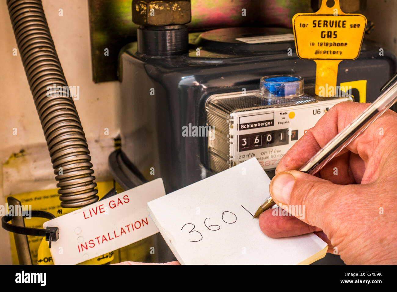 Inside a gas meter cupboard with a yellow key on top of the sealed meter, and a man's hand writing down the consumption reading. England, UK. - Stock Image