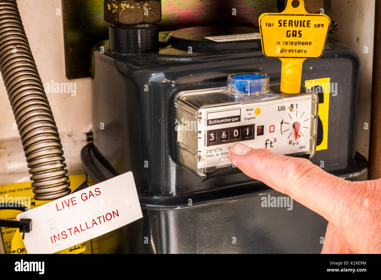 Inside a gas meter cupboard with a yellow key on top of the sealed meter and a finger pointing at the consumption reading. East Midlands, England, UK. - Stock Image