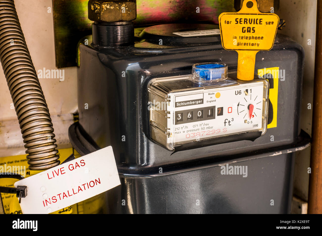 Inside a gas meter cupboard with the yellow key on top of the sealed meter and the consumption reading displayed. East Midlands, England, UK. - Stock Image