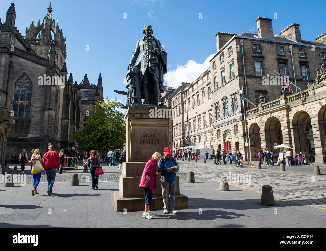 Tourists under the Adam Smith statue on Edinburgh's Royal Mile. - Stock Image