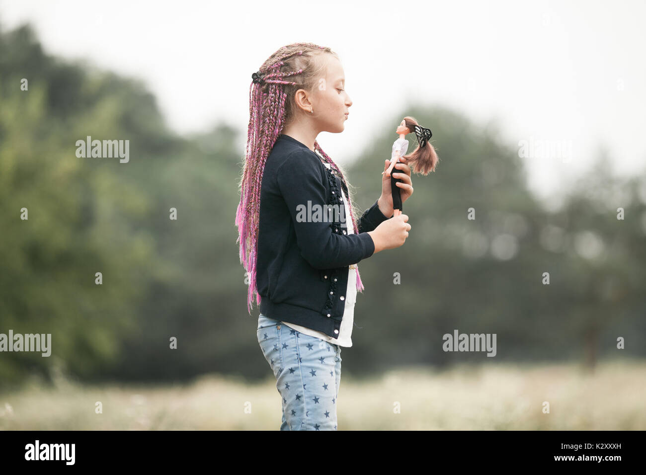 Child girl with pigtails plays with her doll on walk. - Stock Image