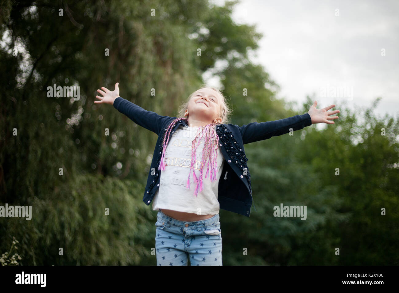Child girl smiles, feels happy, joy and pleasure on walk. She opened her hands to side and closed her eyes. - Stock Image