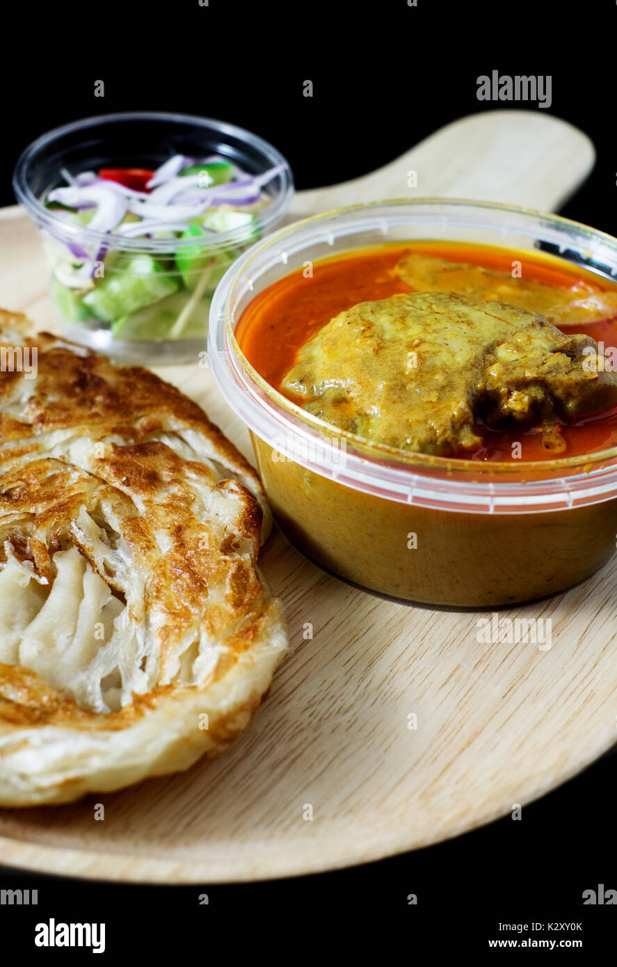 red curry chicken serve with roti and sour sauce on black background - Stock Image