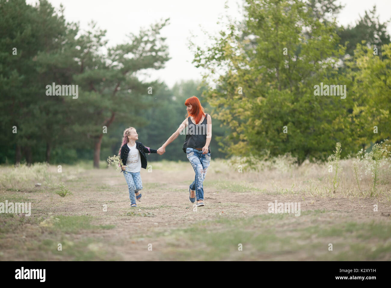Happy girl with her mother laughing fun, hold hands and run along forest road on walk. - Stock Image