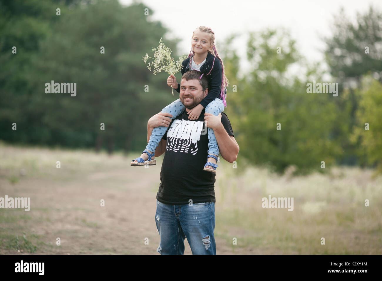 Happy father with daughter smile on walk in park. Dad put child girl on his shoulders. - Stock Image