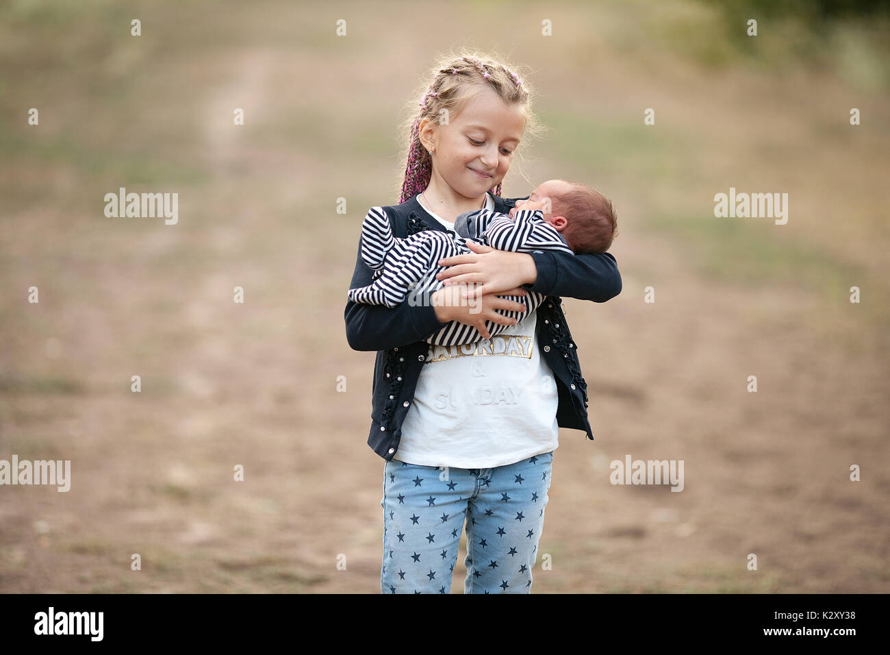 Child girl with her newborn brother on walk. Girl holds newborn baby in her hands and looks him with love. Close up. - Stock Image