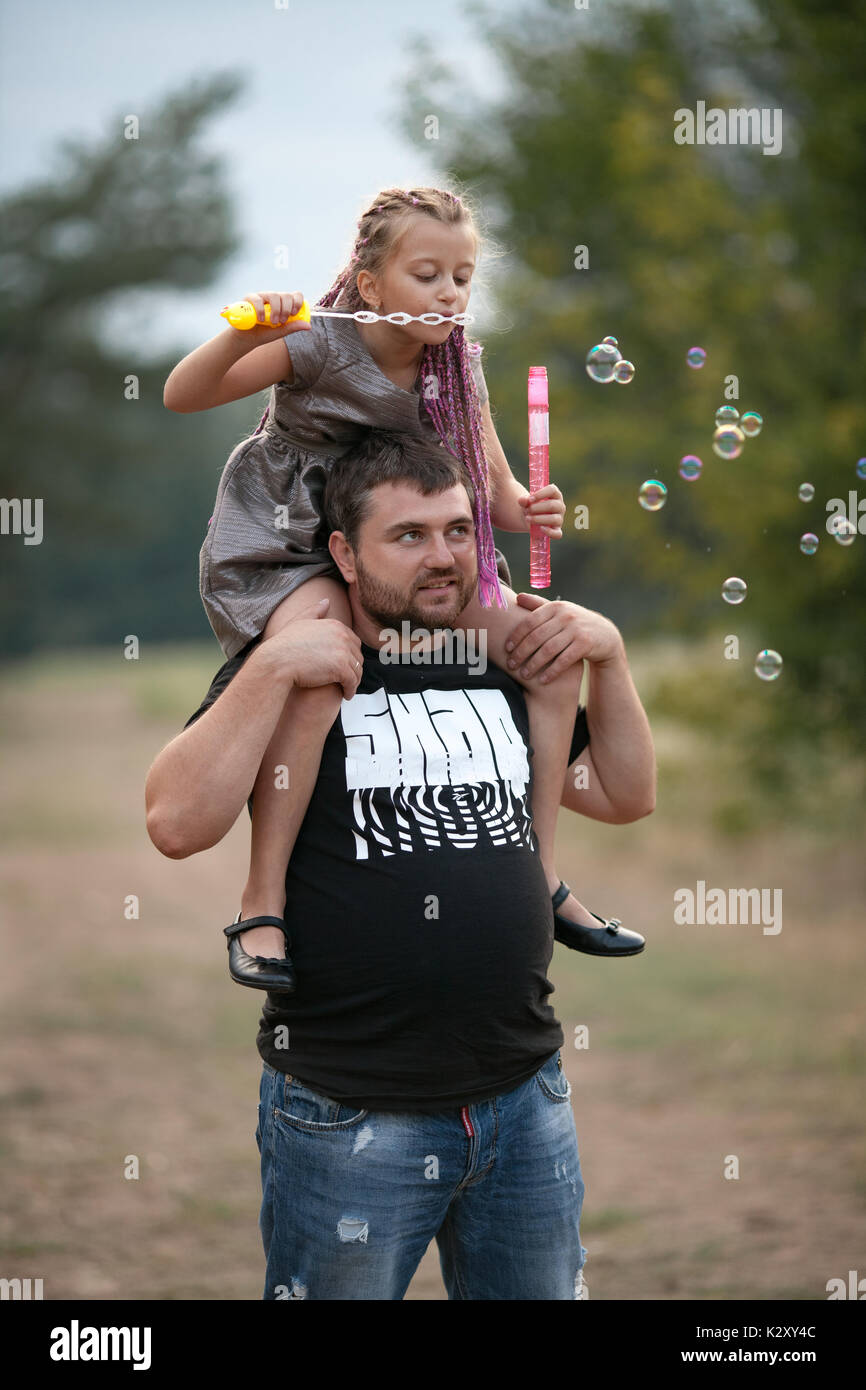 Happy father with daughter blowing soap bubbles on walk in park. Dad put child girl on his shoulders. - Stock Image