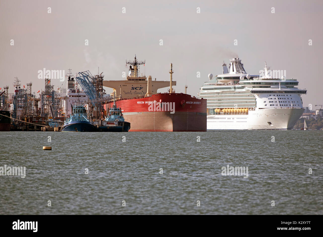 Cruise liner Navigator of the Seas passing the Russian tanker ship Moscow University alongside the Fawley Marine Terminal on Southampton Water, UK - Stock Image