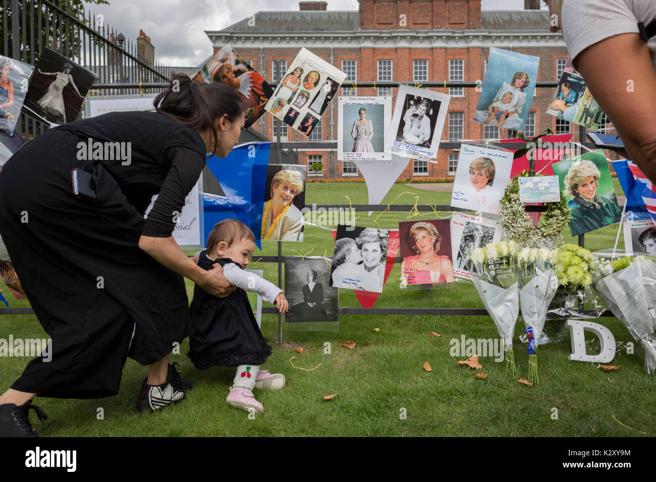 As crowds of royalist well-wishers gather, a spontaneous memorial of flowers, photos and memorabilia grows outside Kensington Palace, the royal residence of Princess Diana who died in a car crash in Paris exactly 20 years ago, on 31st August 2017, in London, England. In 1997 a sea of floral tributes also filled this area of the royal park as well as in the Mall where her funeral passed. Then, as now - a royalists mourned the People's Princess, a titled coined by the then Prime Minister Tony Blair. - Stock Image