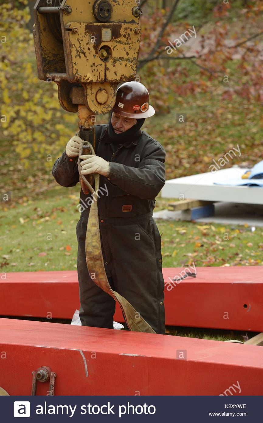 A construction worker wearing a jumpsuit and a helmet locks a strap into a crane in order to lift a large tall red metal beam in installation of John Henry's tall red sculpture entitled 'Red Sails', on the grass outside at Johns Hopkins University campus next to the Levi Building and the Chemistry Building, Baltimore, Maryland, 2013. - Stock Image