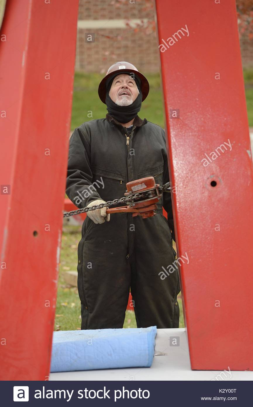 A construction worker wearing a jumpsuit and a helmet and headwrap holds a chain while looking up at the large tall red metal beam in installation of John Henry's tall red sculpture entitled 'Red Sails', on the grass outside at Johns Hopkins University campus next to the Levi Building and the Chemistry Building, Baltimore, Maryland, 2013. - Stock Image