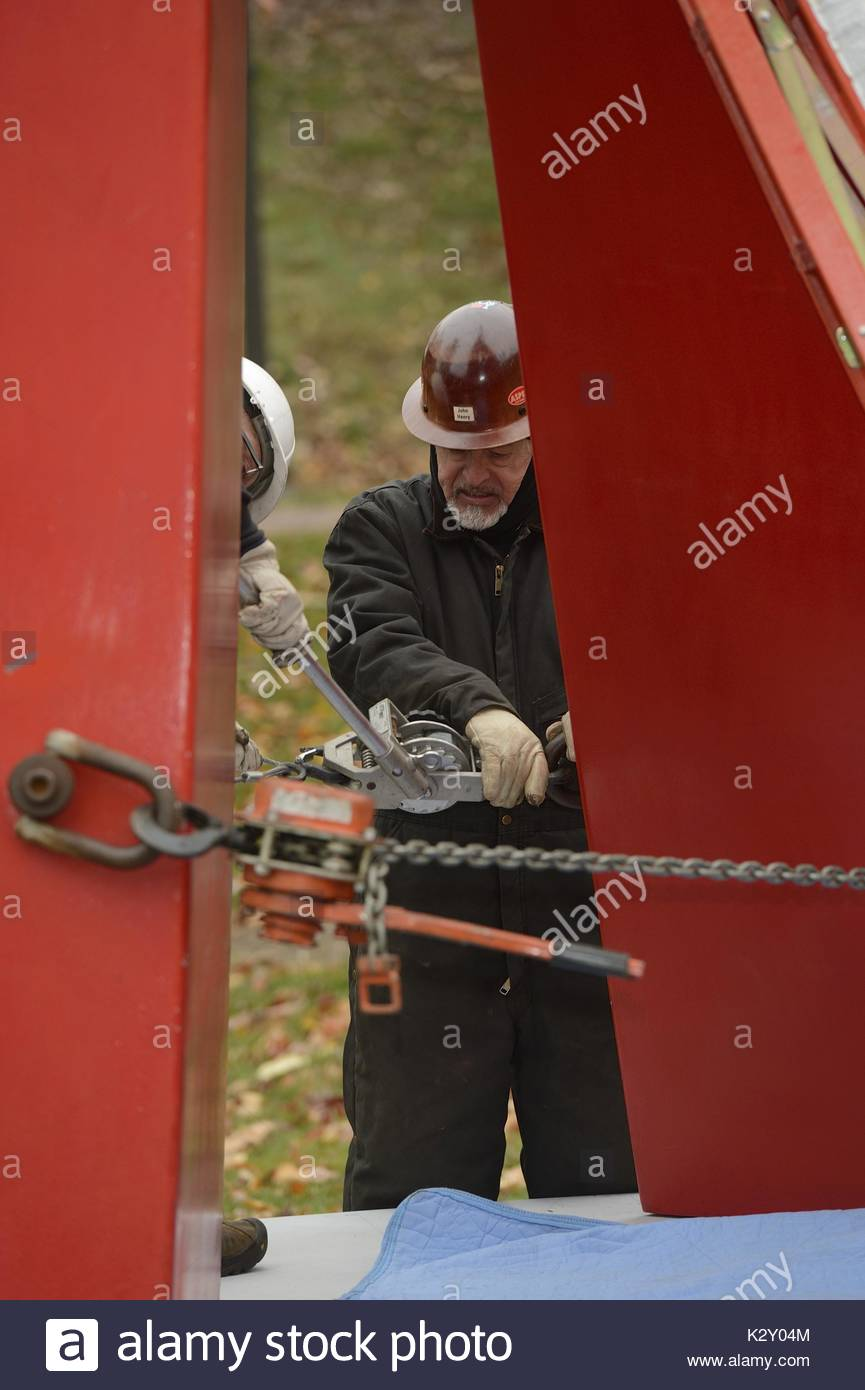 A construction worker wearing a jumpsuit and a helmet and headwrap adjusts a chain around large red metal beams with the help of another construction worker in the installation of John Henry's tall red sculpture entitled 'Red Sails', on the grass outside at Johns Hopkins University campus next to the Levi Building and the Chemistry Building, Baltimore, Maryland, 2013. - Stock Image