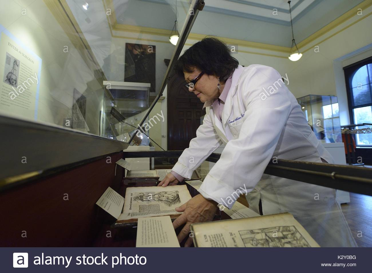 A conservator wearing a white coat bends over an opened glass case as she handles a rare book on display at the George Peabody Library in an exhibit called The Dawn of Neurosurgery, Baltimore, Maryland, 2013. - Stock Image