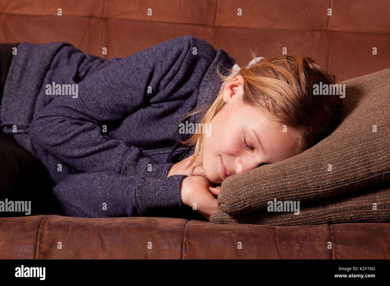 Female teenager sleeping on a sofa or couch. - Stock Image
