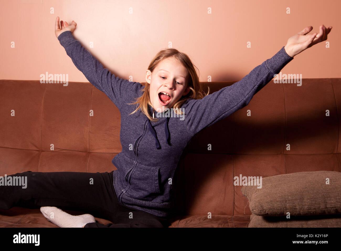teenage girl with blond hair yawning - Stock Image