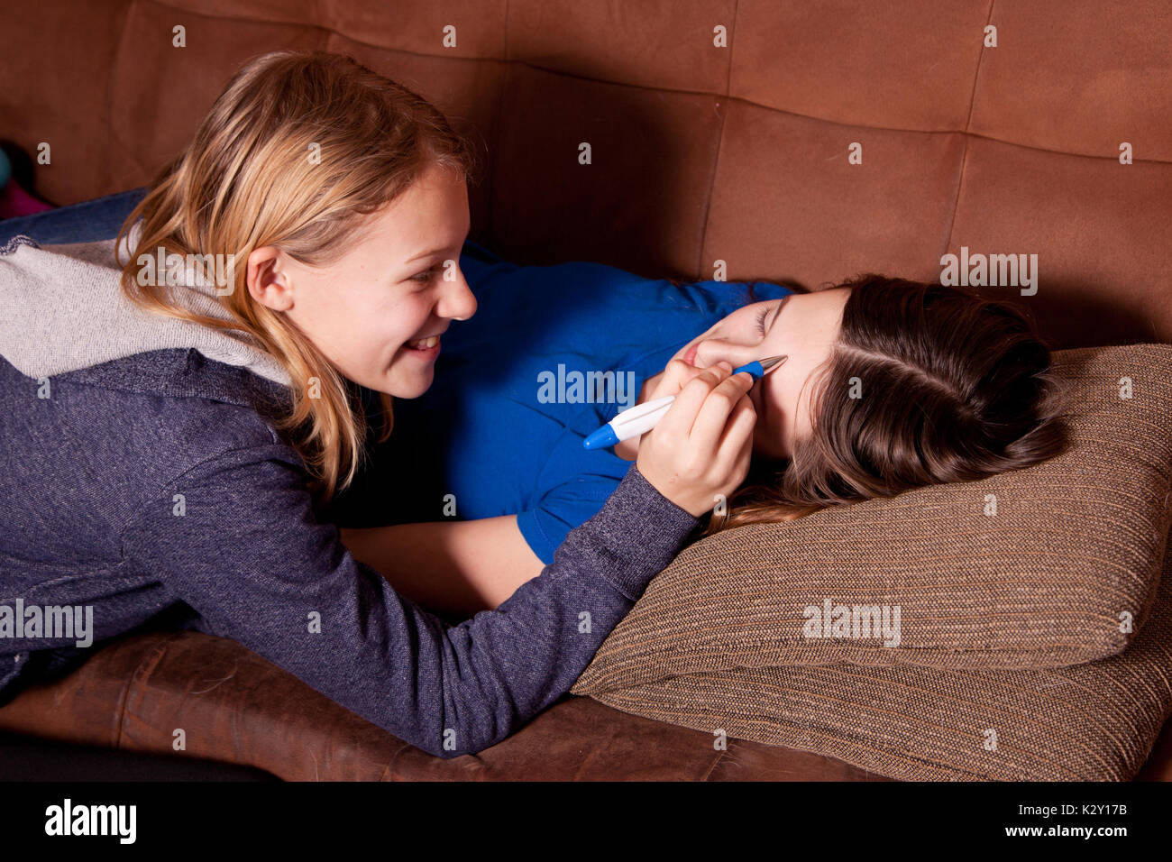 Pesky Little Sister Writes On Sisters Forehead While Asleep Or Sick Stock Image