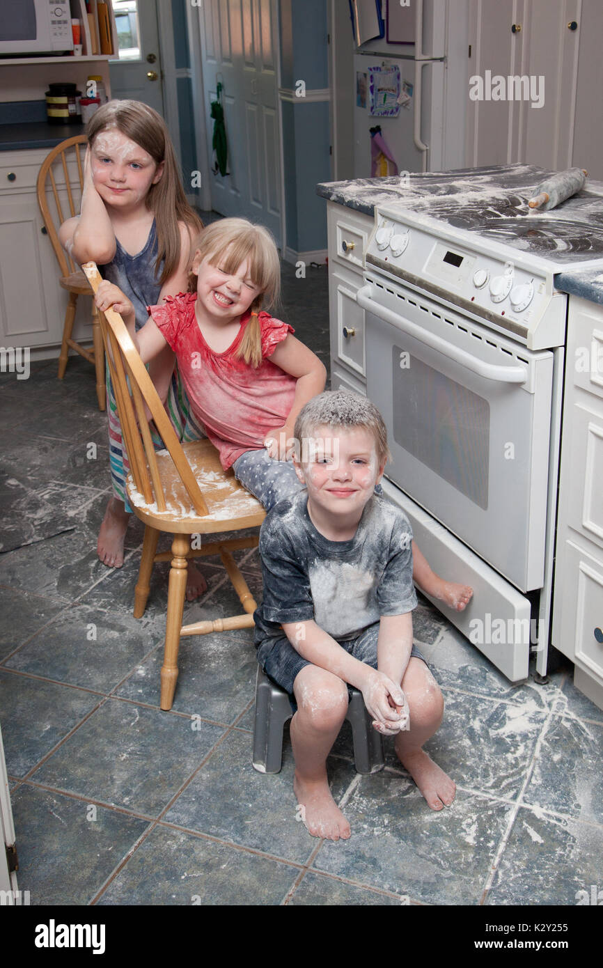 Three naughty children who have just made a mess in the kitchen sit beside the oven looking happy Stock Photo