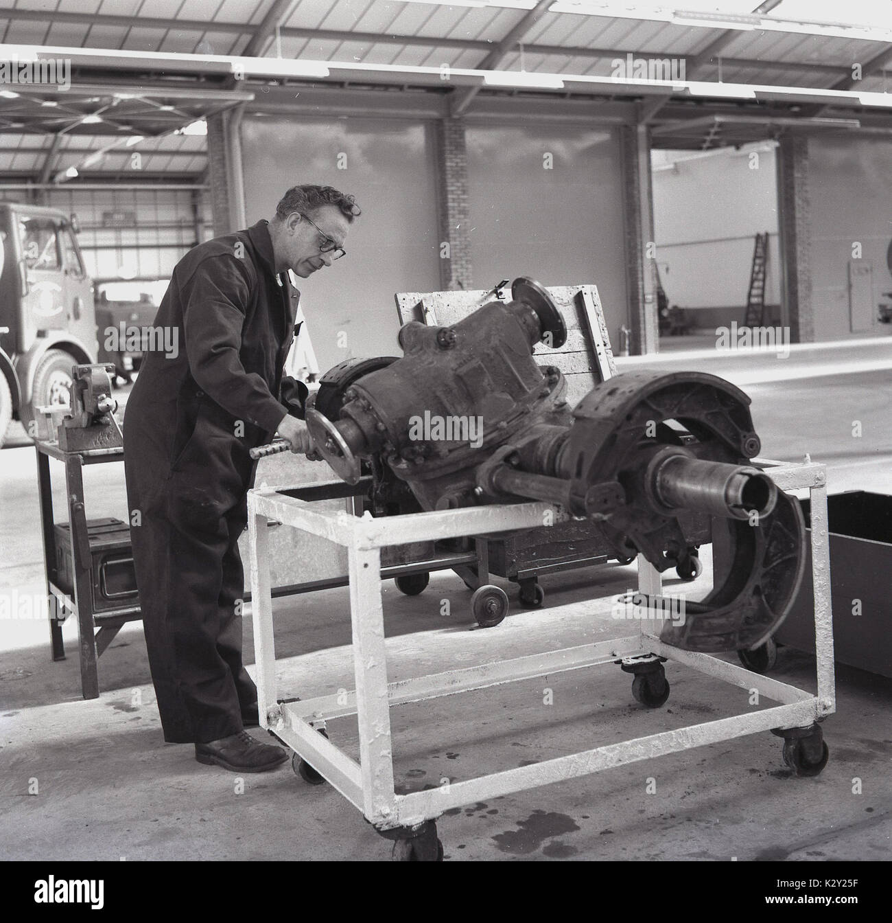 1960s, historical, male motor mechanic checking a large heavy front truck axle and associated parts inside a workshop, England, UK. - Stock Image