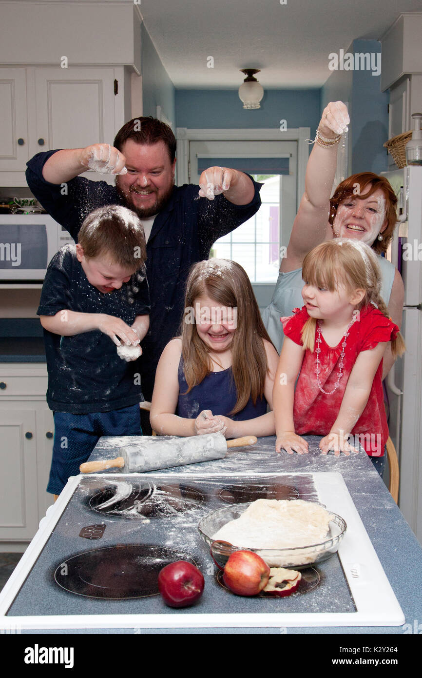 laughing Family food fight with flour in the kitchen. - Stock Image